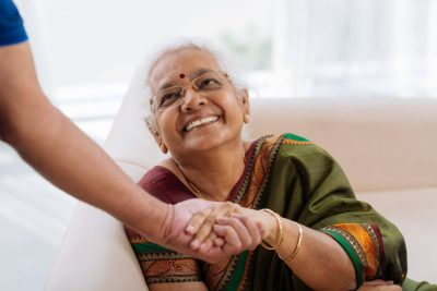 a smiling elderly lady holding a hand