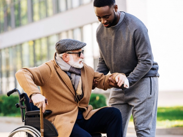 an elderly man with a beard being helped by a male carer